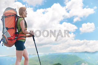 Happy young hiking woman with backpack