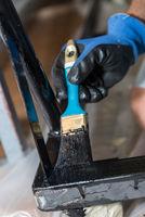 Mit einem Malerpinsel Metallteile schwarz lackieren - Nahaufnahme
