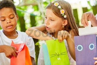 Mädchen als Geburtstagskind packt ein Geschenk aus