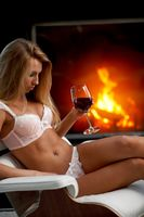 Woman with wine near fireplace