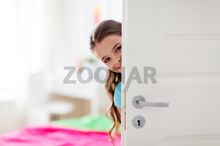 happy smiling beautiful girl behind door at home
