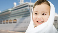 Happy Mixed Race Chinese and Caucasian Boy Near Cruise Ship Wrapped In A Towel