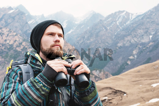 A hipster man with a beard in a hat, a jacket, and a backpack in the mountains holds binoculars, adventure, tourism, tracking