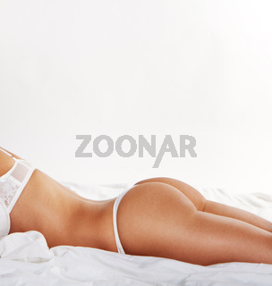 Sexy woman with perfect beautiful shape of body lying on bed