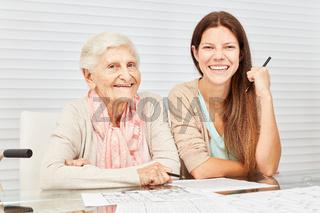 Enkeltochter mit Seniorin beim Rätsel lösen