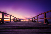 Wooden pier on the sea beach at sunset