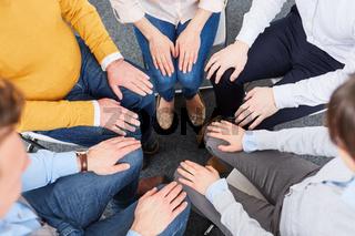 Business Team sitzt im Kreis für Teambuilding