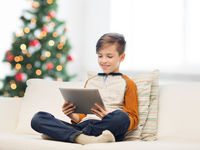 smiling boy with tablet pc at home at christmas
