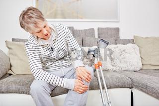 Ältere Frau mit Krücken und Knieverletzung