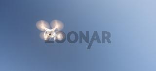 White UAV Quadcopter Drone in Flight Blue Sky