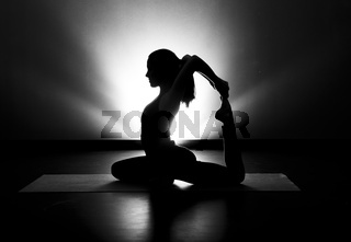 Woman doing yoga pigeon pose silhouette black and white