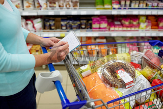 woman with food in shopping cart at supermarket