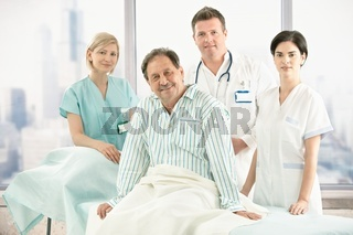 Older patient on bed with hospital crew
