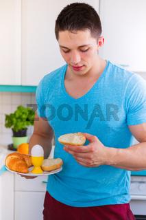 Junger Mann essen Frühstück in der Küche Hochformat morgens Morgen