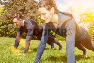 Paar macht Fitnesstraining mit Push-Ups im Sommer
