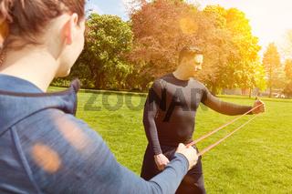 Mann macht Fitness Übung mit Gummiband