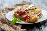 Stack of pancakes and teaspoon with berry jam.