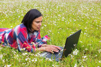 Woman with computer lying in meadow with flowers