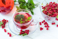 Redcurrant drink in transparent glass carafe and cup