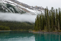 A mist and turquoise water of the Maligne lake, Alberta, Canada