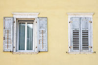 Zwei Fenster mit Fensterläden in einem gelben Haus