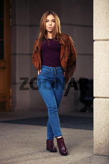 Young fashion woman in leather jacket walking on city street