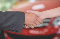 Close up view of handshake of vehicle dealer and buyer in car showroom.