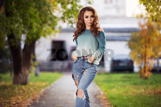 Young fashion woman with long curly hairs walking on city street