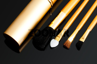 cosmetic brushes on black background