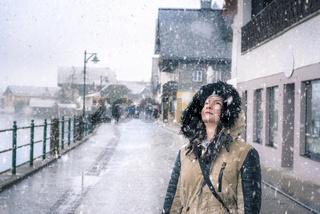Happy woman looking up at snowflakes