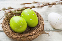 An easter nest with green easter eggs