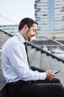 Junger Business Mann tippt eine SMS