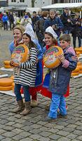 Holländische Käsemädchen posieren mit Gouda Käserädern und zwei Kindern für eine Souvenirfoto