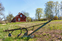 Old horse drawn plow the field with a red cottage