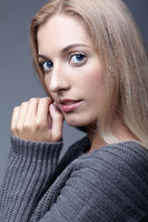 Portrait of young romantic woman in gray woolen sweater. Beautiful girl posing on grey studio background. Female with blonde hair and day beauty makeup touching face
