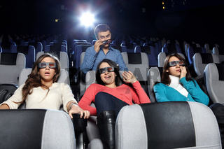 The young man observes of the attractive girl at cinema