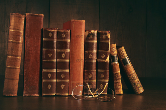 Stack of old books with glasses on desk