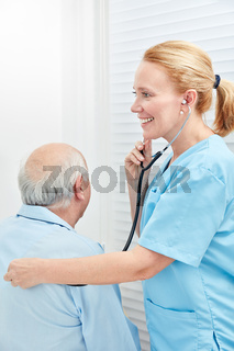 Pflegehilfe hört Patient mit dem Stethoskop ab