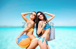 happy young women in bikini posing on summer beach