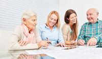 Senioren Paar und Enkelin lösen Rätsel zusammen