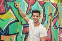 Young muscle man leaning on graffiti wall
