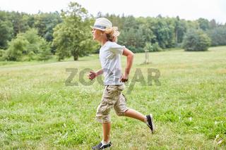 Blonder Junge läuft über eine Wiese