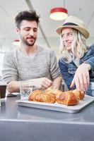 Junges Paar hat Hunger und isst Croissants