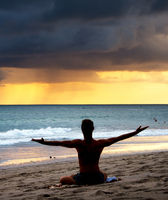 Man doing yoga at beach
