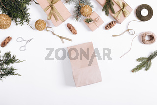 Christmas decorations on a white background: paper bag, fir branches, gift boxes, ribbons, toys, rope, scissors