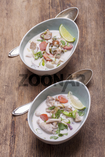 thai tom kha gai soup on wood