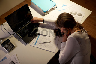 tired woman sleeping on office table at night