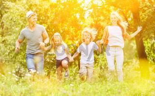 Familie und Kinder laufen über Wiese im Sommer