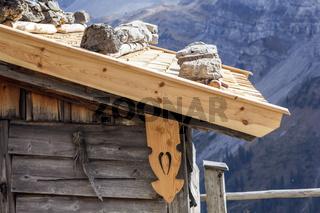 Ein mit Steinen beschwertes Holzdach einer Hütte in den Alpen.