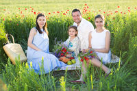 Portrait of a young pregnant family in poppy field